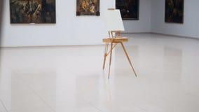 Steadicam het schieten van de schildersezel met wit canvas op het Het bevindt zich in het centrum van de galerij 4K stock videobeelden