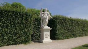 Steadicam in koninklijke tuin, rond wit marmeren standbeeld van vrouw wordt geschoten die stock videobeelden