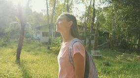 Young woman walking on countryside path through asian village, slow motion. Steadicam portrait shot of young backpacker woman walking alone on a countryside stock footage