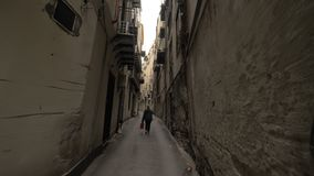 Walking through the alleyway with old houses in Palermo, Italy. Steadicam POV shot of walking along the narrow alleyway with shabby houses walls and following stock video