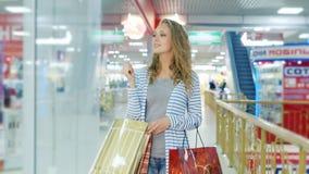 Steadicam schoot: De aantrekkelijke jonge vrouw met vele het winkelen zakken gaat langs storefrontswinkelcentrum stock videobeelden