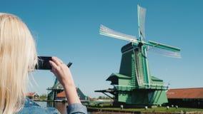 Steadicam schoss: Frau macht Fotos von alten Windmühlen in Zaans Schans stock footage
