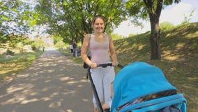 Steadicam schoss von der glücklichen jungen Frau, die mit Babysohn im Spaziergänger auf Park geht stock footage