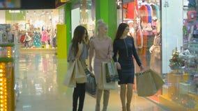 steadicam schot Jonge gelukkige dames die in een opslag met het winkelen zakken lopen Langzame Motie stock footage