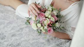 An attractive, sexy bride in a boudoir lies on the bed and touches a beautiful wedding bouquet of pink and white roses. Steadicam shot of an attractive, sexy stock video footage