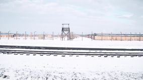 Steadicam shot of concentration camp fence, guard tower and railroad tracks in winter. 4K video. Steadicam shot of concentration camp fence, guard tower and stock video footage
