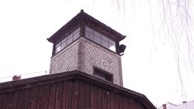 Steadicam shot of concentration camp watch tower in falling snow. 4K clip stock footage