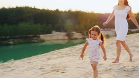 Steadicam shot: happy childhood, mother playing with her daughter on the beach. Girl laughs and runs away from his stock video footage