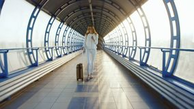 Steadicam shot: Life in motion. Stylish woman with travel bag is on the sunlit move between terminals.  stock video footage
