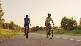 Steadicam shot of mountain biking couple riding on bike trail at sunset doing high.  stock footage