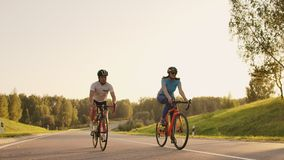 Steadicam shot of mountain biking couple riding on bike trail at sunset doing high.  stock video