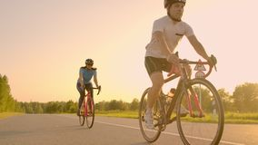 Steadicam shot of mountain biking couple riding on bike trail at sunset doing high.  stock video footage