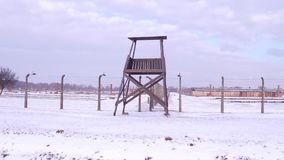Steadicam shot of old guard tower and barbed wire fence of a concentration camp in winter. 4K video. Steadicam shot of old guard tower and barbed wire fence of a stock video