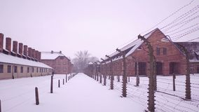 Steadicam shot of old rusty barbed wire fences and concentration camp buildings. Brick barracks and lonely man in