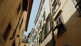 Steadicam shot: An original narrow street with old houses in the historic part of Florence. stock footage
