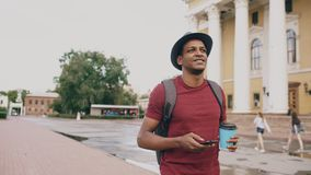 Steadicam shot of smiling student in hat walking and surfing smartphone drinking coffee outdoors. Steadicam shot of mixed race student in hat walking and surfing Royalty Free Stock Photos