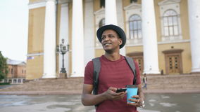 Steadicam shot of smiling tourist man walking and surfing smartphone near famous historical place in Europe stock footage