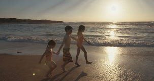 Steadicam shot of three young kids running on the beach during sunset