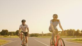 Steadicam shot of two healthy mem and woman peddling fast with cycling road bicycle at sunset. Steadicam shot of two healthy mem and woman peddling fast with stock video