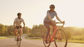 Steadicam shot of two healthy mem and woman peddling fast with cycling road bicycle at sunset. Steadicam shot of two healthy mem and woman peddling fast with stock footage