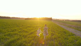 Steadicam shot of two sisters walking in a green field during sunset stock video footage