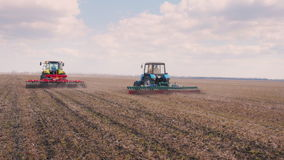 Steadicam shot: Two tractors go ahead on the field, cultivate the ground stock video