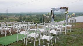 Steadicam shot of a variety of white folding chairs in the reception area of the marriage on the wedding ceremony with. Drops of rain. Wet seat under the open stock video