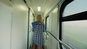 Steadicam shot: a woman with a towel is walking along the train of a passenger train. Early morning on the way. Rear. A woman with a towel is walking along the stock video footage