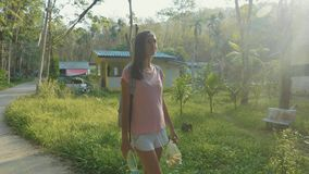 Young woman walking on countryside road through asian village, slow motion. Steadicam shot of young backpacker woman walking alone on a countryside road through stock video footage
