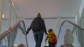 Steadicam shot of a young woman and her little son going up using an escalator in an airport.  stock footage