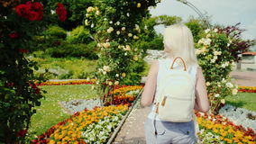 Steadicam shot: A young woman is walking in the garden of roses. Uses a mobile phone. Graz, Austria stock video footage