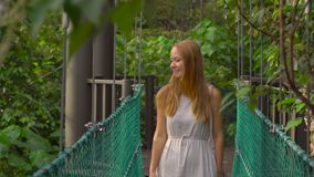 Steadicam shot of a young woman walking on the hanging suspension bridge in the Eco Park in the Kuala Lumpur city.  stock video footage