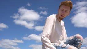Steadicam sköt av en ung röd haired stilish man mot bakgrund för blå himmel lager videofilmer
