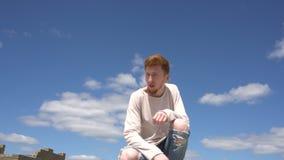Steadicam sköt av en ung röd haired stilish man mot bakgrund för blå himmel stock video