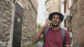 Steadicam skott av turisten för blandat lopp som går och pratar telefonen Ung lycklig manresande i Europa stock video