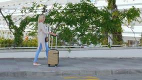 Steadicam skott: Den unga kvinnan med resväskan på väghjulen är på trottoaren Spanien semesterort Begrepp - ankomst till stock video