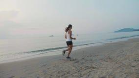 Steadicam strzał młoda atrakcyjna kobieta jogging na plaży przy wschodem słońca zbiory