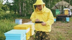 Steadicam strzał pszczelarka mężczyzna sprawdza ule w pasiece z pastylka komputerem zdjęcie wideo