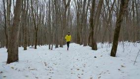 Steadicam a tiré de l'homme barbu dans le manteau jaune fonctionnant dans la forêt neigeuse d'hiver banque de vidéos