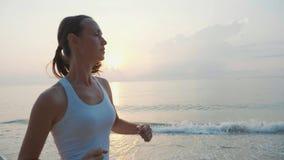 Steadicam a tiré de la jeune femme attirante pulsant sur la plage au lever de soleil banque de vidéos