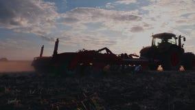 Steadicam a tiré : Le tracteur harrows le champ au coucher du soleil banque de vidéos