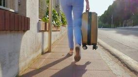 Steadicam a tiré : Touriste de femme marchant sur la route avec un sac de voyage Station de vacances de l'Espagne Vue arrière banque de vidéos