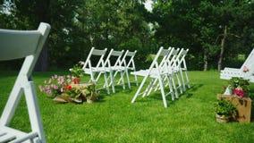 Steadicam tiró: Césped verde con filas de las sillas de madera blancas Lugar para la ceremonia de boda almacen de video
