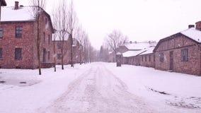 Steadicam tiró de Auschwitz Birkenau, concentración nazi alemana y campo de la exterminación Cuarteles en nieve que cae 4K almacen de video