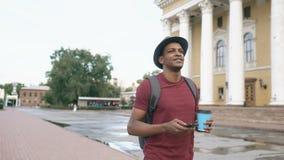 Steadicam tiró de estudiante sonriente en café de consumición del sombrero que caminaba y que practicaba surf del smartphone al a almacen de metraje de vídeo