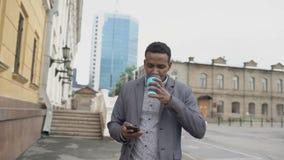 Steadicam tiró de hombre de negocios feliz joven usando smartphone y caminar con la taza de café al aire libre