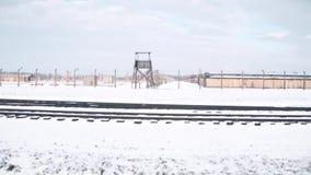 Steadicam tiró de la cerca del campo de concentración, de la torre de guardia y de pistas de ferrocarril en invierno vídeo 4K almacen de metraje de vídeo