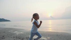 Steadicam tiró de la muchacha del pequeño niño que activaba en la playa en la salida del sol almacen de metraje de vídeo