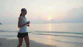 Steadicam tiró de la mujer atractiva joven que activaba en la playa en la salida del sol metrajes
