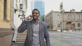 Steadicam tiró del baile alegre del hombre de negocios de la raza mixta y del teléfono que hablaba sobre su nueva carrera almacen de metraje de vídeo